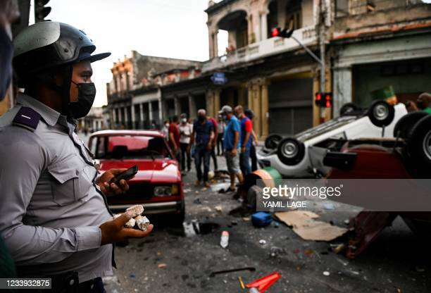 Policeman stands while watching police cars overturned in the street in the framework of a demonstration against Cuban President Miguel Diaz-Canel in...