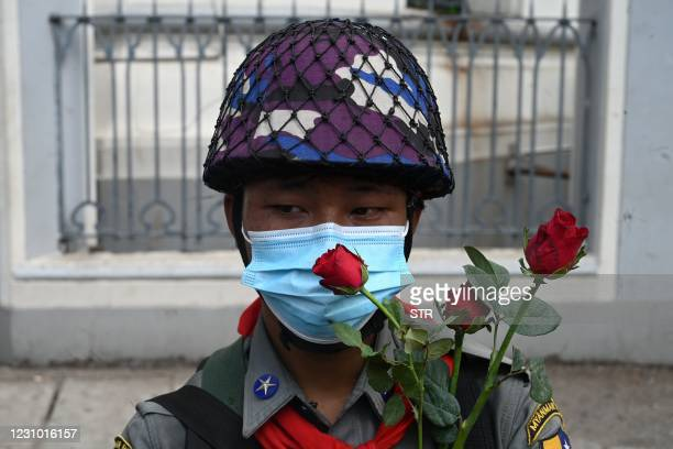 Policeman stands with flowers given to them by protesters during a demonstration against the military coup in Yangon on February 7, 2021.