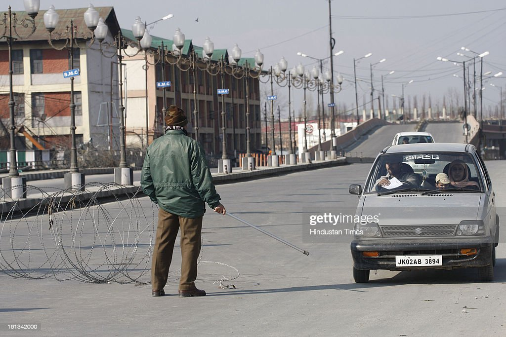 Policeman stop a vehicle for checking after the parliament attack convict, Muhammad Afzal Guru was hanged in New Delhi, during Second day curfew on February 10, 2013 in Srinagar, India. Guru, who was found guilty of conspiring and sheltering the militants who attacked Parliament on December 13, 2001 in which nine people were killed, was buried in the prison premises as per the jail manual.