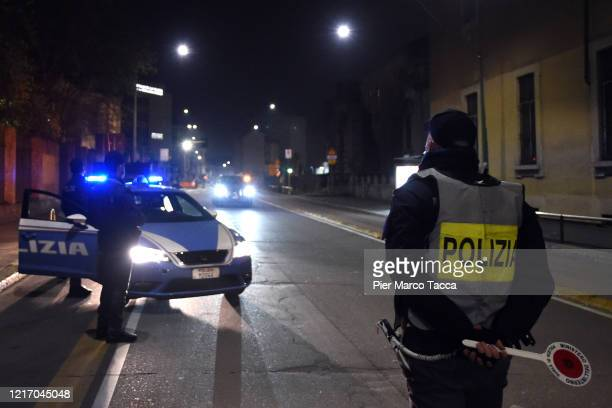 Policeman stops a car during a night checkpoint for the control of the territory during the coronavirus outbreak on April 04, 2020 in Milan, Italy....