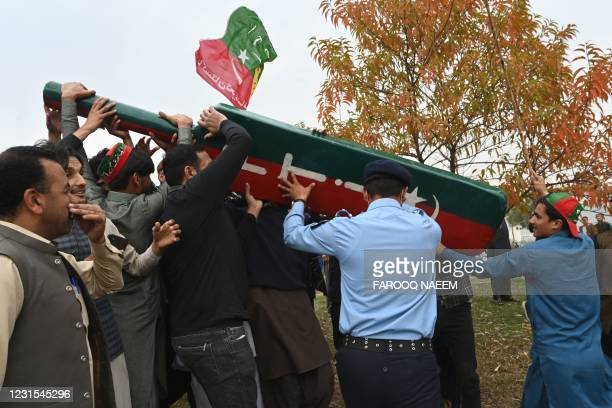 Policeman stops opposition party activist as supporters and activists of the ruling Pakistan Tehreek Insaf party shout slogans as they gather outside...