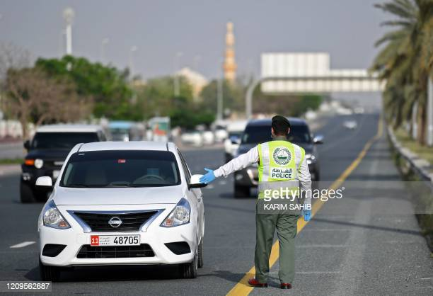 A policeman stops vehicles at a security checkpoint to examine passengers for exit permits as people are only allowed essential travel due to a...