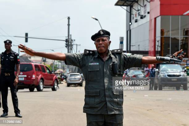 A policeman stretched his arms to stop protesters advancing to a barricade in Port Harcourt Rivers State on March 11 2019 Several thousand people on...