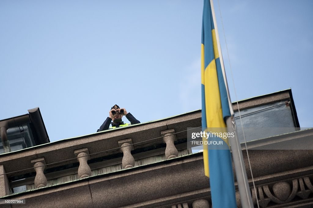 A Policeman surveys the crowds from a rooftop as guests arrive for a gala performance at the Stockholm Concert Hall in Stockholm on June 18, 2010, at the start of the weekend's wedding celebrations. Less than half Sweden's population now supports the monarchy, and a quarter thinks it a bad thing, a poll showed today amid preparations for Crown Princess Victoria's nuptials this weekend.