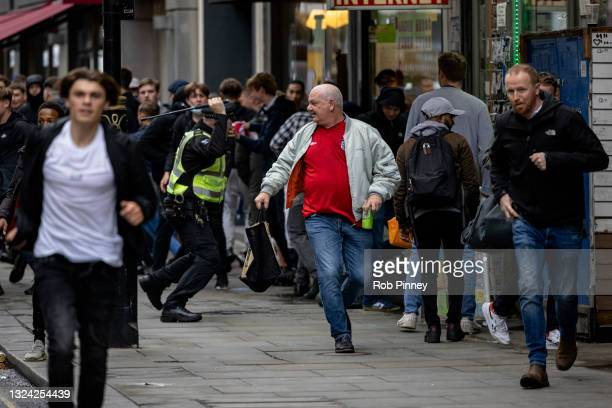 Policeman tackles a group of England fans as they attempt to run towards Scotland fans gathered in Leicester Square on June 18, 2021 in London,...