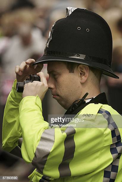 A policeman takes a picture of the crowd on April 21 2006 in Windsor England HRH Queen Elizabeth II is taking part in her traditional walk in the...