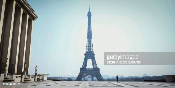 A policeman takes a picture of the landmark Eiffel Tower from the deserted Esplanade du Trocadero in Paris on March 28 on the twelfth day of a...