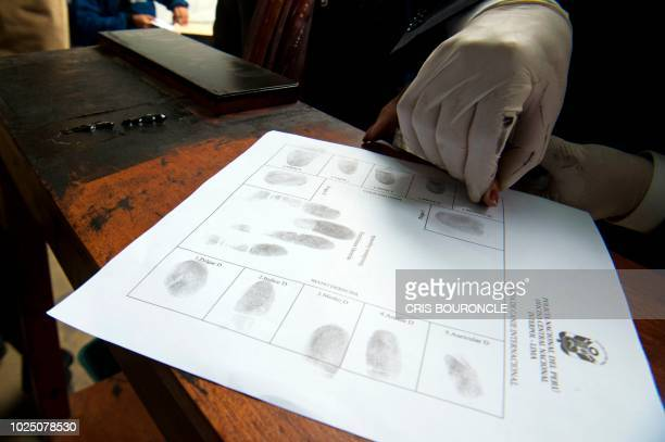A policeman takes fingerprints of a Venezuelan migrant while applying for a resident visa or temporary stay permits at an Interpol facility in Lima...