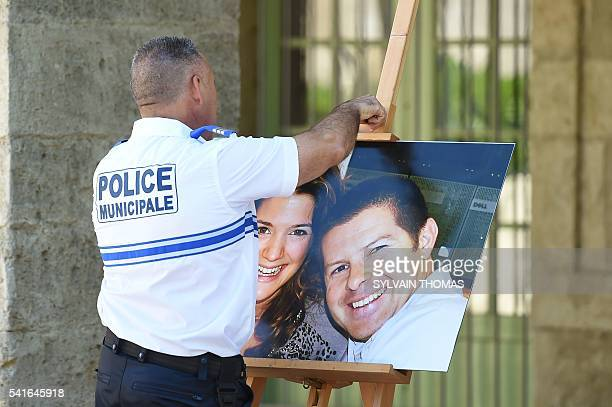 A policeman takes off the picture of French policeman JeanBaptiste Salvaing and his partner Jessica Schneider who were killed outside their home in...