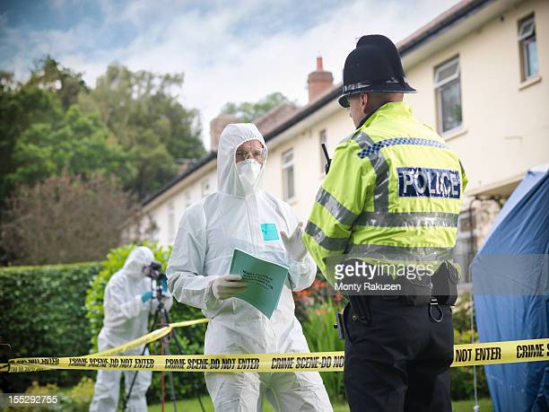 policeman talking to forensic scientists at crime scene - crime scene stock pictures, royalty-free photos & images