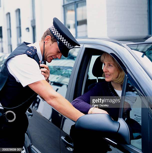 Policeman talking to mature woman in car and using radio