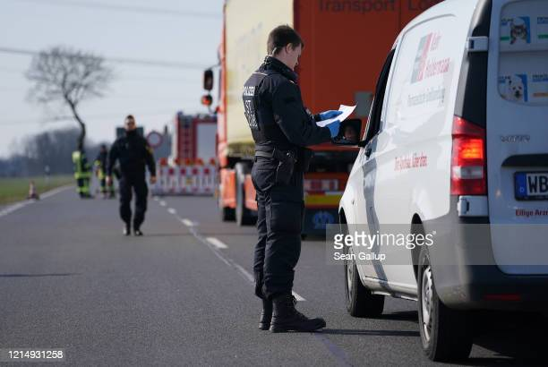 A policeman talks to a driver at a checkpoint on a road leading to the quarantined towns of Schweinitz and Jessen on March 26 2020 near Jessen...