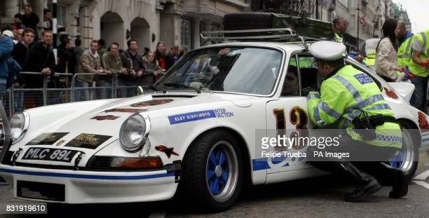 A policeman talks to a participant at the start of the car rally Gumball 3000 at Pall Mall in London
