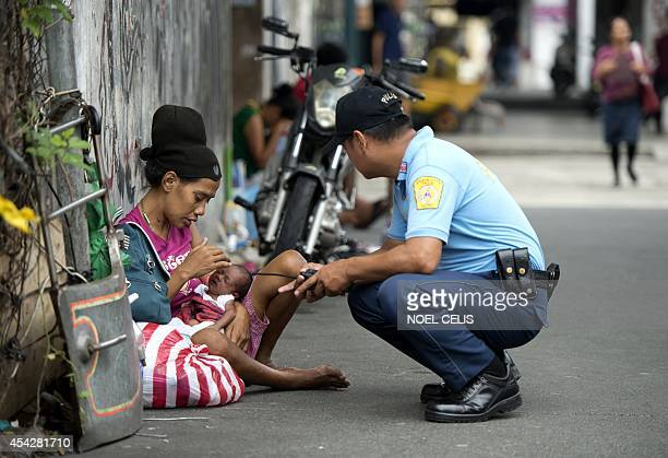 A policeman talks to homeless woman Inday Ibayo holding her onemonthold baby along a street in Manila on August 28 2014 The Philippine economy...