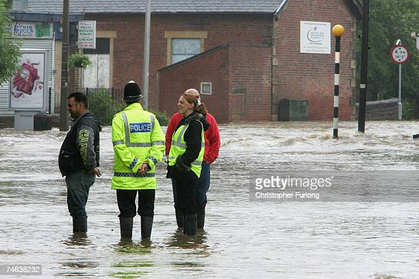 Policeman talks to residents of the village of Darton, South Yorkshire, as flood waters rise on June 15 in Darton, England. Britain suffered a deluge...