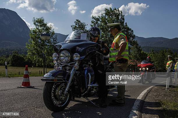 A policeman talks with a motorbike rider at a checkpoint ahead of the upcoming summit of G7 nation leaders on June 4 2015 in GarmischPartenkirchen...