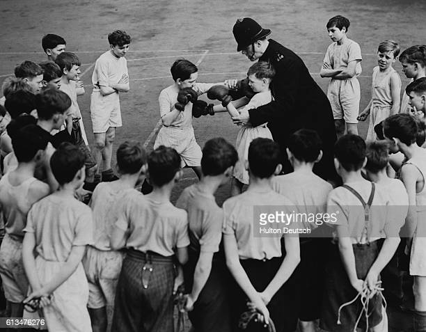 A policeman teaches boxing to London schoolboys