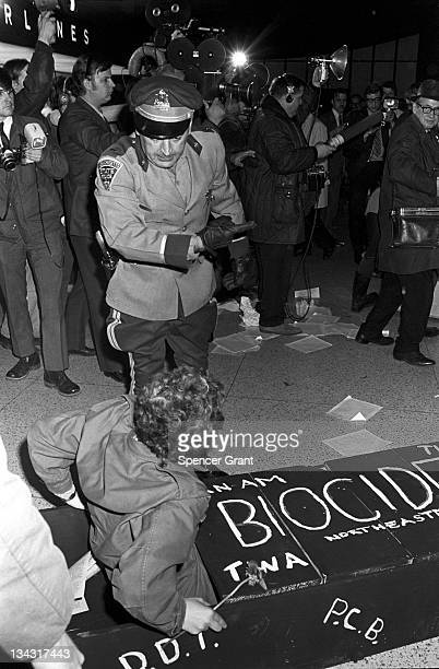 A policeman tells an Earth Day protestor to leave the premises at Logan Airport in Boston 1970