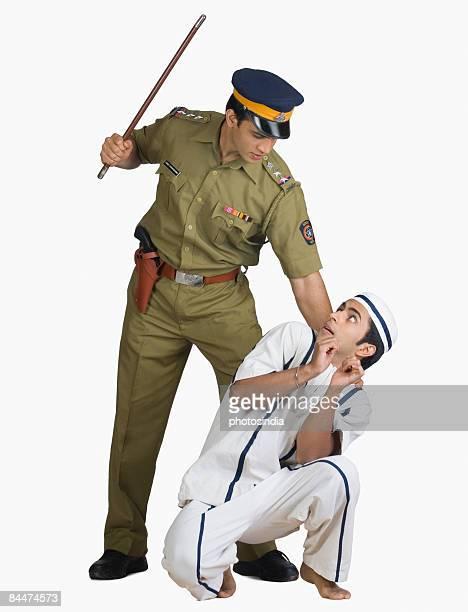 Policeman threatening a prisoner