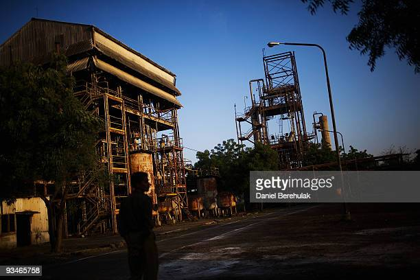 A policeman tours the site of the deserted Union Carbide factory on November 28 2009 in Bhopal India Twentyfive years after an explosion causing a...