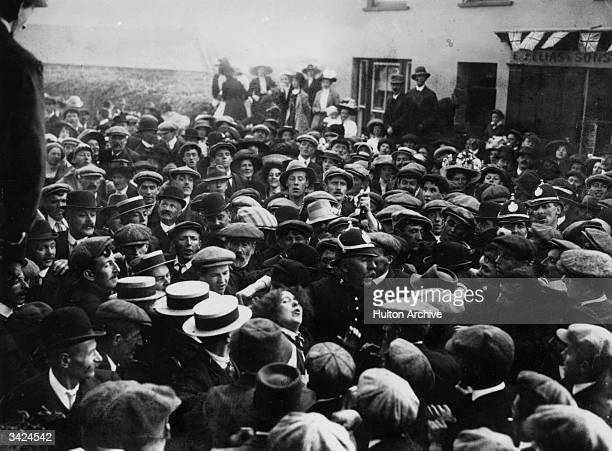 A policeman tries to lead a suffragette on whom the crowd has turned to safety at a meeting given by Chancellor of the Exchequer David LloydGeorge at...