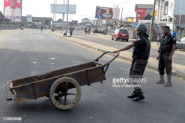 A policeman tries to mount a blockade with a cart on a road in Port Harcourt Rivers State on March 9 during voting to elect governors and lawmakers...