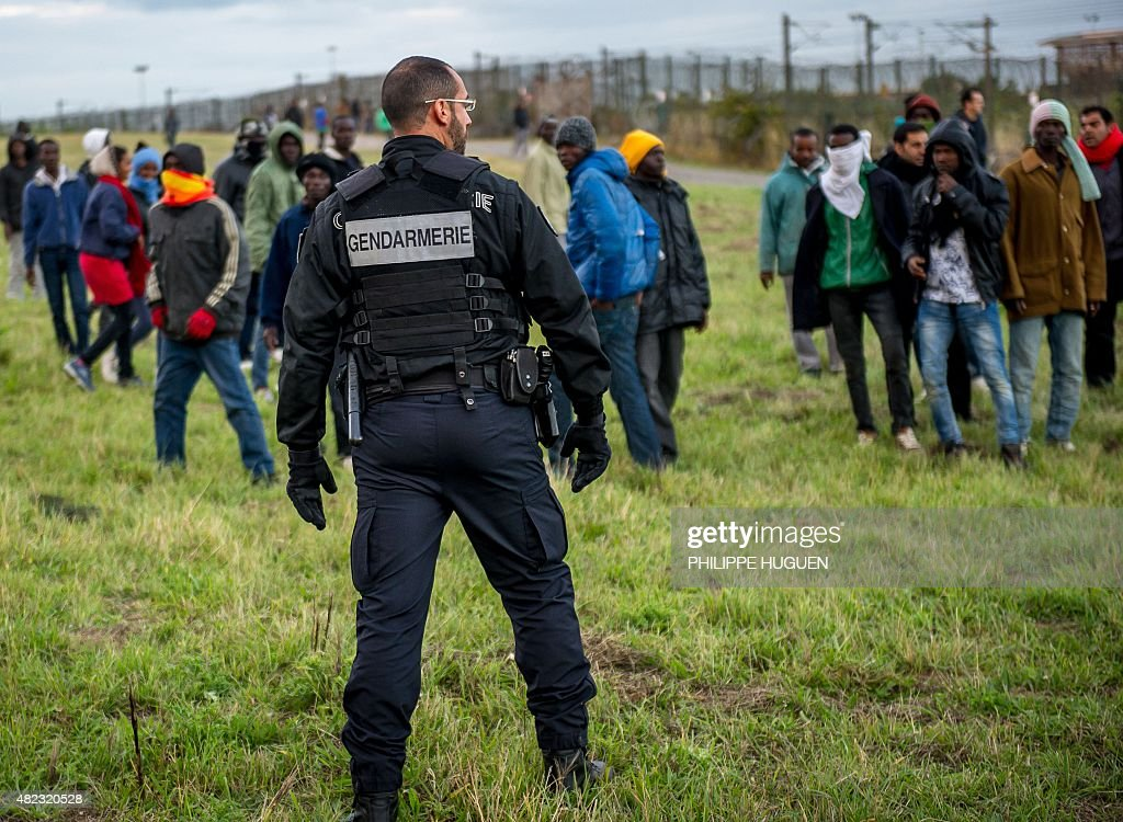 A policeman tries to stop migrants on the Eurotunnel site in Coquelles near Calais, northern France, on late July 29, 2015. One man died Wednesday in a desperate attempt to reach England via the Channel Tunnel as overwhelmed authorities fought off hundreds of migrants, prompting France to beef up its police presence.