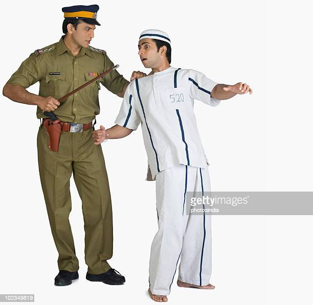 Policeman tugging a prisoner from collar
