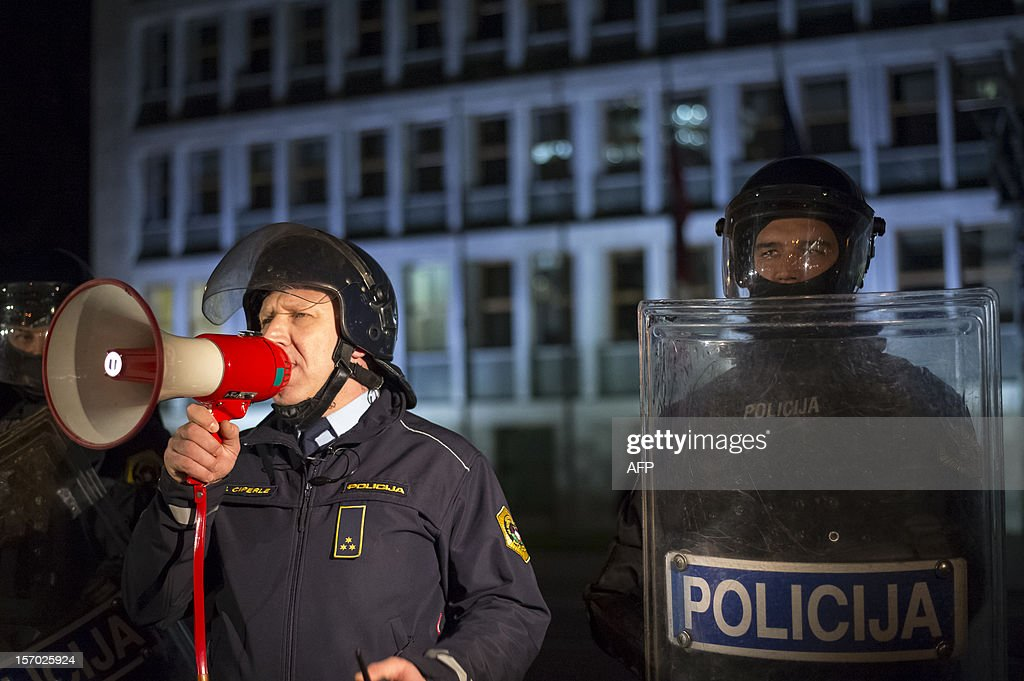 A policeman uses a megaphone to calm down protesters during a protest against Slovenian police who used tear gas in Maribor to disperse a thousands-strong rally calling for the resignation of centre-right mayor Franc Kangler, on November 27, 2012 in Ljubljana. AFP PHOTO Jure Makovec