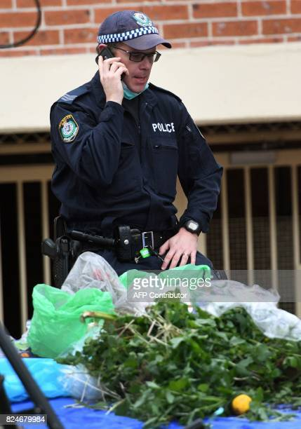 A policeman uses his photo as authorities search for evidence at a block of flats in the Sydney suburb of Lakemba on July 31 after counterterrorism...