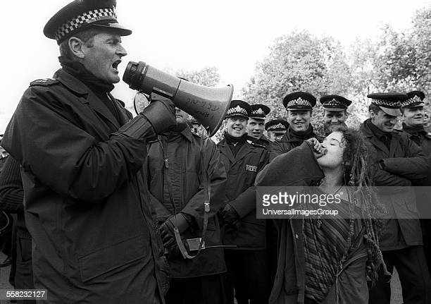 A policeman using a megaphone while a demonstrator makes fun of him Criminal Justice Rally Hyde Park London UK 1994