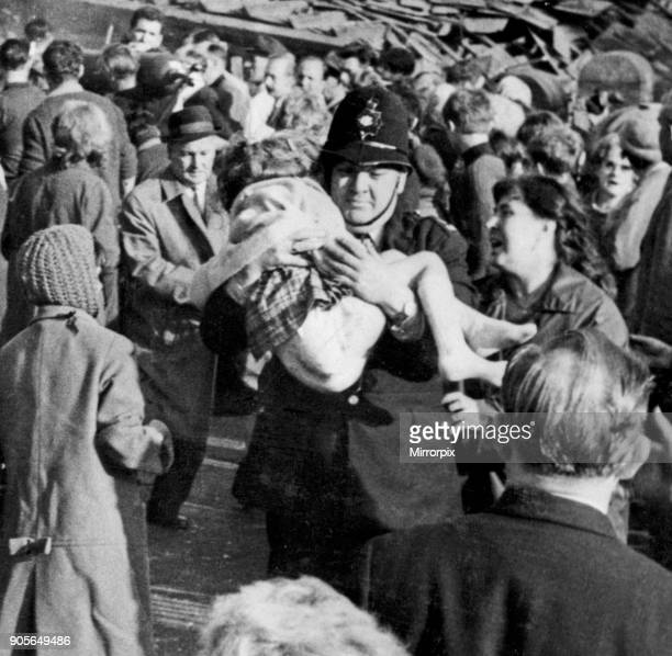 Policeman Victor Jones carries a little girl from the wrecked school as woman anxiously looks to see if she can recognise her Picture taken by...