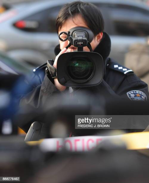 A policeman videotapes foreign journalists outside a Beijing court which upheld an appeal on the 11year jail term for leading Chinese dissident Liu...