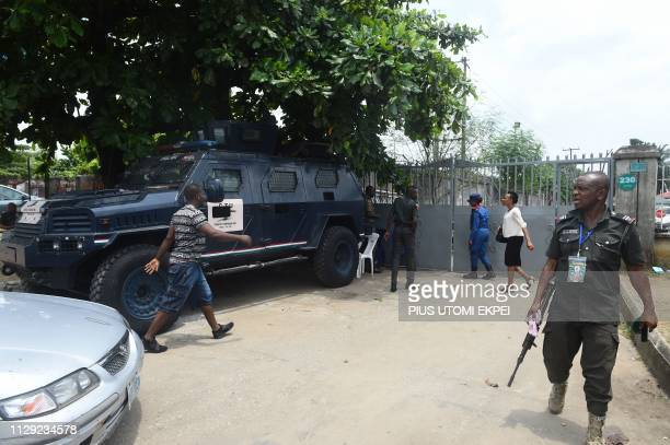 A policeman walk past an Armoured Personnel Carrier parked at the main gate of the Independent National Electoral Commission headquarters in Port...