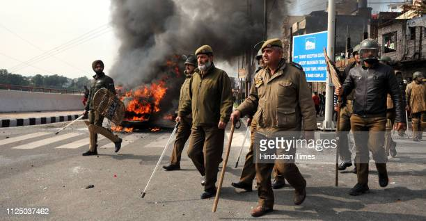 Policeman walk past as vehicles go up in flames after scores of them were set ablaze by an angry mob during a protest against the killing of CRPF...