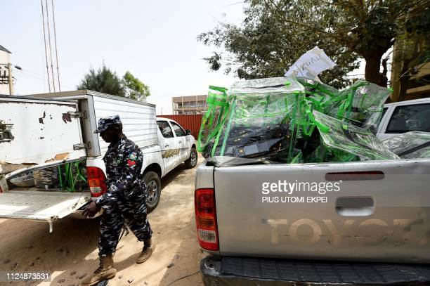 A policeman walk past ballot boxes and card readers loaded onto a truck at the headquarters of Independent National Electoral Commission in Kano...