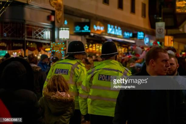 policeman walking through crowds at birmingham christmas market - west midlands stock pictures, royalty-free photos & images
