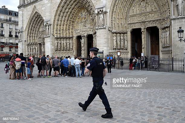 A policeman walks by the Notre Dame Cathedral as people wait in line prior to a Mass with the archbishop of Paris to pay tribute to the priest...