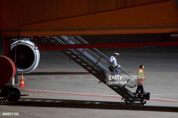 A policeman walks down the stairs of the Turkish Airlines aircraft on the runway to bring German human rights activist Peter Steudtner to the Tegel...