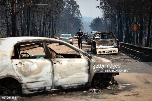 TOPSHOT A policeman walks on a road past burnt cars after a wildfire in Figueiro dos Vinhos on June 18 2017 A wildfire in central Portugal killed at...