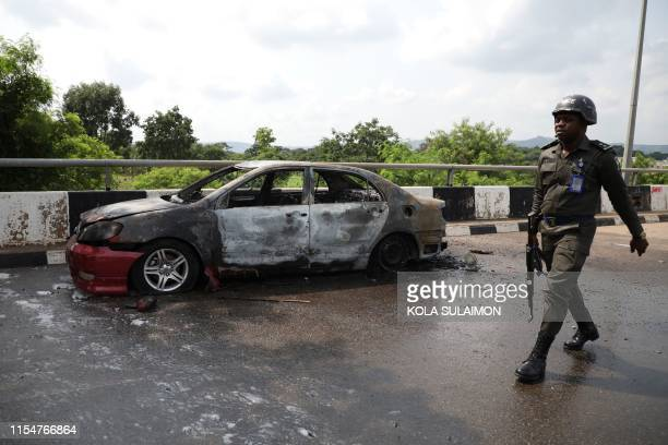 Policeman walks past a car burnt by supporters of an imprisoned leader of the Islamic Movement of Nigeria Ibrahim Zakzaky around the national...