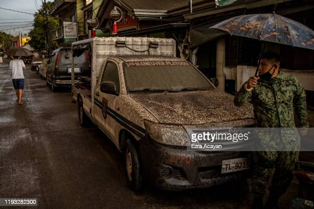 A policeman walks past a police vehicle covered in ash mixed with rainwater as Taal Volcano erupts on January 12 2020 in Talisay Batangas province...
