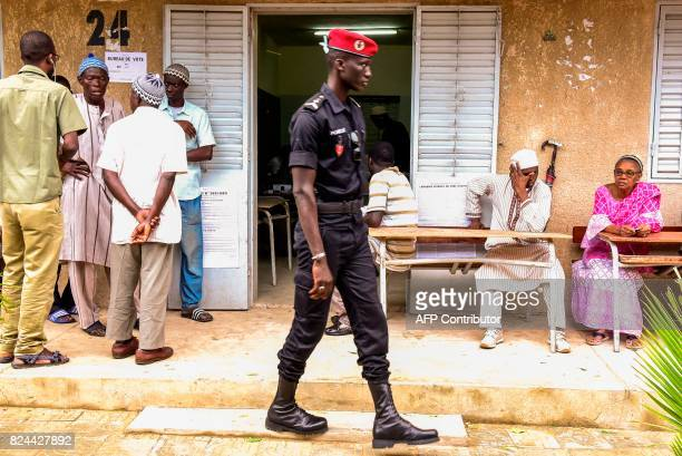 A policeman walks past a polling station as people wait prior to casting their vote in Senegal's legislative election on July 30 2017 in Dakar...