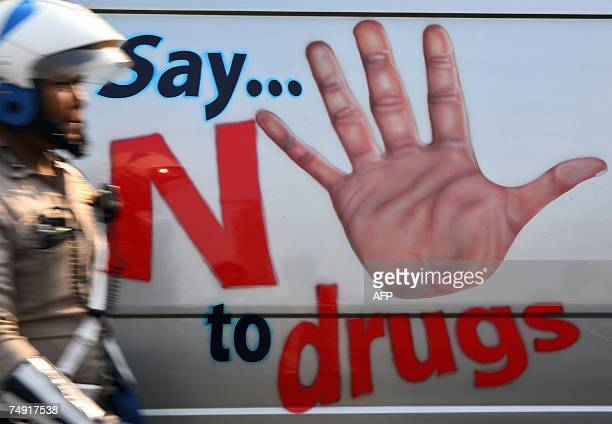 A policeman walks past antidrugs campaign poster to mark the United Nations international antidrugs day in Jakarta 25 June 2007 Indonesia has...