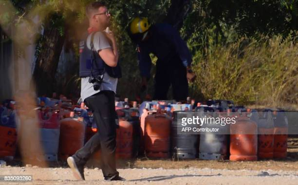 A policeman walks past dozen of gas bottles in Alcanar during a search linked to the Barcelona and Cambrils attacks on the site of an explosion on...