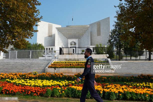 Policeman walks past in front of the Supreme Court building during a case hearing suspending the notification of the tenure extension of Chief of...