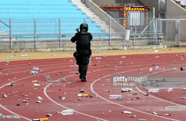 A policeman walks past rubbish on the ground following the Tunisia Ligue 1 football match derby between Esperance Sportive de Tunis and Club Africain...