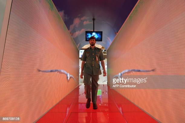 A policeman walks through a security tunnel at the Gitex 2017 exhibition at the Dubai World Trade Center in Dubai on October 10 2017 Travellers...