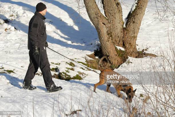 A policeman walks with a dog outside the house of Norwegian multimillionaire Tom Hagen in Fjellhamar on January 10 2019 as his wife AnneElisabeth...