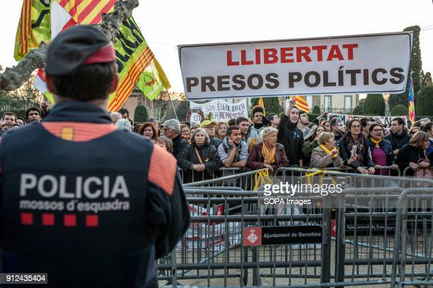 A policeman watch the crowd during a demonstration to support Carles Puigdemont former Catalan President in front of the Catalonia Parliament in...